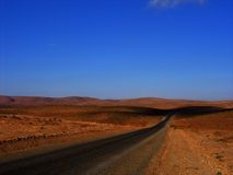 Southern Moroccan desert road. Road in the southern Moroccan desert stretching to the horizon Stock Photo