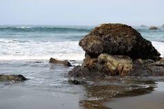 Southern Oregon Beach. Dark barnacle encrusted boulder fronts blue ocean foaming waves on Oregon's southern coastal region Royalty Free Stock Image