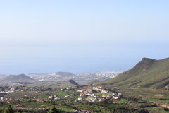 Southern part of Tenerife island with small villages at mountain slopes and Las Americas city on the Atlantic coast, aerial view f Stock Images