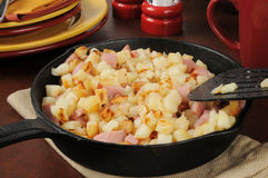 Southern style hash browns and ham. Southern style hash browns with ham in a cast iron skillet stock photos