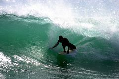 Southshore Surfer. Surfer in silhouetted in late afternoon back lit wave on Oahu Stock Image