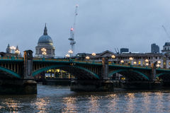 Southwark Bridge and St Pauls Cathedral at Dusk. Southwark Bridge Illuminated by Street Lights and Spanning Across Thames River with View of Historic St Pauls Stock Image