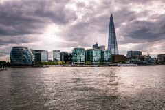 Southwark and the Thames dramatic mood in London. Southwark distict under the clouds. London city in spring, United Kingdom royalty free stock photo