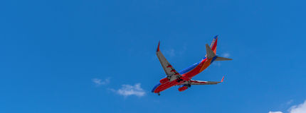 Southwes Boeing jet in midair descending. Taken from downtown San Diego, California approaching the airport stock photography