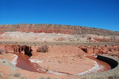 Southwest Cliff Scene With Red Curved River. A red clay river bends in front of a southwestern cliff with horizontal striations. The river is lined with alkali Royalty Free Stock Photos
