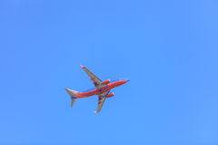 Southwest jet flying through the clouds across a blue sky Stock Image