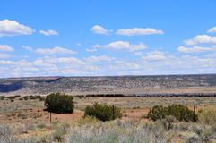 Southwest Landscape with Train. Traveling across country with blue sky with clouds and telephone wires crossing the landscape Royalty Free Stock Photos