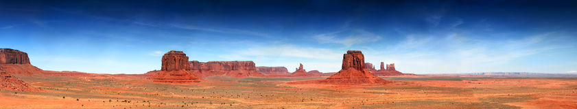 Southwest Panorama of Monument Valley. Desertscape panorama of the Arizona southwest Monument Valley with blue sky and wispy clouds Royalty Free Stock Image