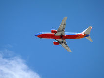 Southwest Plane flies overhead with wheels dropped royalty free stock photo