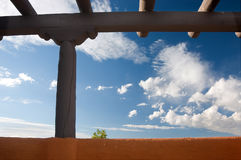 Southwestern adobe. Southwestern architecture. Beams and earth colored wall against blue sky, one little tree showing up behind the wall. New Mexico stock photography