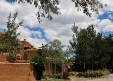 Southwestern adobe architecture under a blue sky with fluffy white clouds and surrounded and framed by trees.  Stock Image