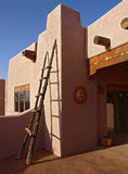 Southwestern home. Southwestern style adobe walled home and ladder Stock Image