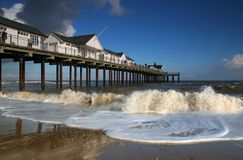 Southwold Pier with Breakers. Southwold Pier in Suffolk, UK. White pier buildings against a blue sky with waves breaking on a sandy beach in the forground Royalty Free Stock Image