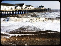Southwold pier and rough sea on a cold winter day. Large waves around the pier at Southwold Royalty Free Stock Photography