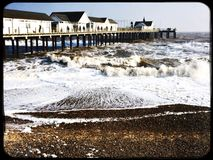 Southwold pier and rough sea on a cold winter day. Large waves around the pier at Southwold Royalty Free Stock Photos