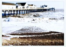 Southwold pier and rough sea on a cold winter day. Large waves around the pier at Southwold Royalty Free Stock Image