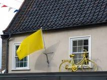 SOUTHWOLD, SUFFOLK/UK - 11 DE JUNHO: Bandeira amarela e bicicleta em um H Fotos de Stock Royalty Free