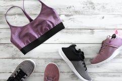 Soutien-gorge du sport des femmes et deux paires de violette, de noir et de wh d'espadrilles Photographie stock libre de droits