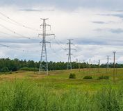 Soutient les lignes électriques à haute tension contre le ciel bleu avec des nuages industrie électrique images stock