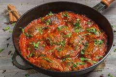 Soutzoukakia griego las empanadas en salsa de tomate en la cacerola imagenes de archivo