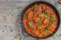 Soutzoukakia griego las empanadas en salsa de tomate en la cacerola Cierre para arriba La visión desde la tapa Copia-espacio imagenes de archivo
