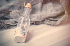 Souvenir bottle and fishnet on the sand Royalty Free Stock Images