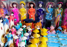 Souvenir dolls in traditional clothes in Vietnam. Vietnamese souvenirs – dolls in traditional Vietnam hats and clothes of different colors standing in a line Stock Photos