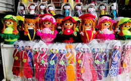 Souvenir dolls in traditional clothes in Vietnam. Vietnamese souvenirs – dolls in traditional Vietnam hats and clothes of different colors standing in a line Stock Photo