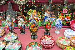 Souvenir eggs and boxes paintinted with flowers. Souvenirs wooden board painted with colorful flowers and birds sold on the street in Andreevsky spusk in Kiev Stock Photos