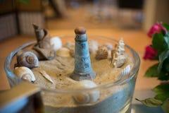 Souvenir från semester, fyr med havsskalet och sand Royaltyfri Fotografi
