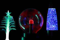 Souvenir lamps of different form. Three souvenir lamps of different form: conifer,  round  red and cylindrical blue  on black background Stock Images