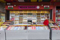 Souvenir rock stall. Rhyl, Wales, U.K- May, 20, 2014 : Welsh  Woman in red coat selling sticks of candy from a rock stall Royalty Free Stock Photo