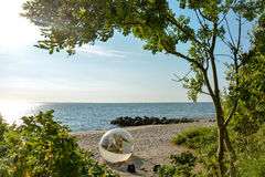 Souvenir sculpture - Aarhus Denmark. The sculpture Souvenir is a glass ball with a seemingly newborn world just arrived with the morning sun on the beach at the Royalty Free Stock Photography