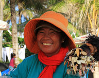 Souvenir seller at the beach. In Kuta, Bali Indonesia. Old asian woman smiling at the camera Royalty Free Stock Image