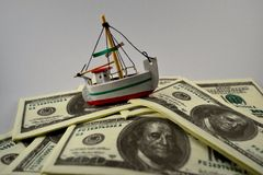 Souvenir ship sailing on fake Dollar bills Stock Photo