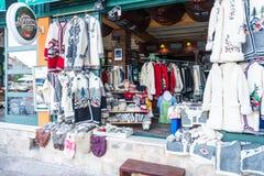 Souvenir shoppar och person som tillhör en etnisk minoritetkläder i det turist- området av Budva Montenegro Royaltyfri Fotografi