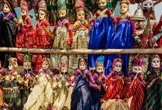 Souvenir toys of traditional Indian market. Faces of funny handmade dolls in old costumes for children in Asia.  royalty free stock image