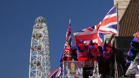 Souvenir Union Jacks and London  Eye. Union Jacks fly from a souvenir stall with the London Eye rotating in the background. Shot in 4K on a sunny September stock video footage