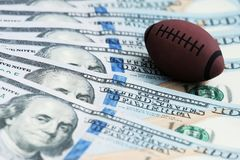 Souvenirboll för att spela rugby eller amerikansk fotboll på USA-sedlar Begreppet av att slå vad för korruption eller för sportar royaltyfri bild