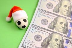 Souvenirfotbollboll i en röd Santa Claus hatt bredvid dollar på en grön bakgrund Slå vad för begreppssportar eller en julklapp arkivfoton