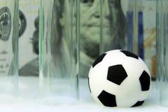 Souvenirfotbollboll med medicinska provrör mot bakgrunden av hundra dollarräkning Begreppspengar och sportar, medicin Fotografering för Bildbyråer