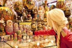 Souvenirladen im alten Arbat Moskau blondes Mädchen wählt Andenken Lizenzfreie Stockbilder