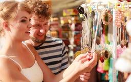 Souvenirs de achat de jeunes couples extérieurs Image stock