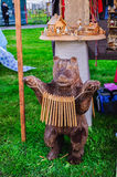 Souvenirs at the Russian fair - wooden sculpture of a bear playing a ratchet. Veliky Novgorod, Russia. VELIKY NOVGOROD, RUSSIA - JUNE 11, 2016. Souvenirs at the Stock Images