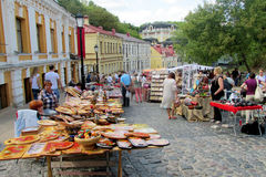 Souvenirs on the street in Andreevsky spusk in Kiev, Ukraine. Souvenirs wooden board painted with colorful flowers and birds sold on the street in Andreevsky stock illustration