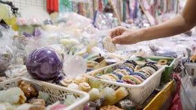 Souvenirs thaïlandais faits main de achat de jeune femme au marché asiatique de nuit Bangkok, Thaïlande 4K clips vidéos