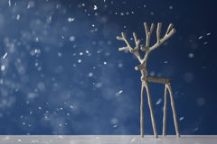 Souvenirsilverhjortar på en blå bakgrund i snö Arkivbilder