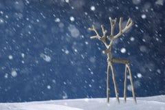 Souvenirsilverhjortar på en blå bakgrund i snöstorm Arkivbild