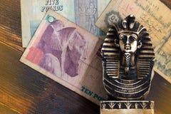 Souvenirskulptur av den egyptiska farao på pengarbakgrunden Arkivbilder