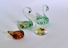Souvenirsvanar gjorde av exponeringsglas med färgrika ägg som gjordes av exponeringsglas arkivfoton